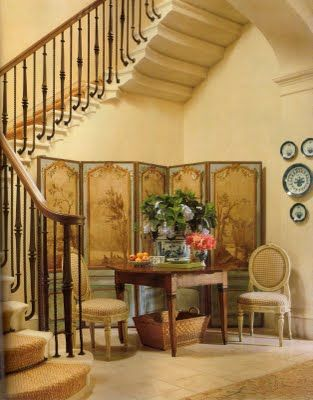 Such a beautiful entry/staircase with screen, table and chairs, blue and white china.