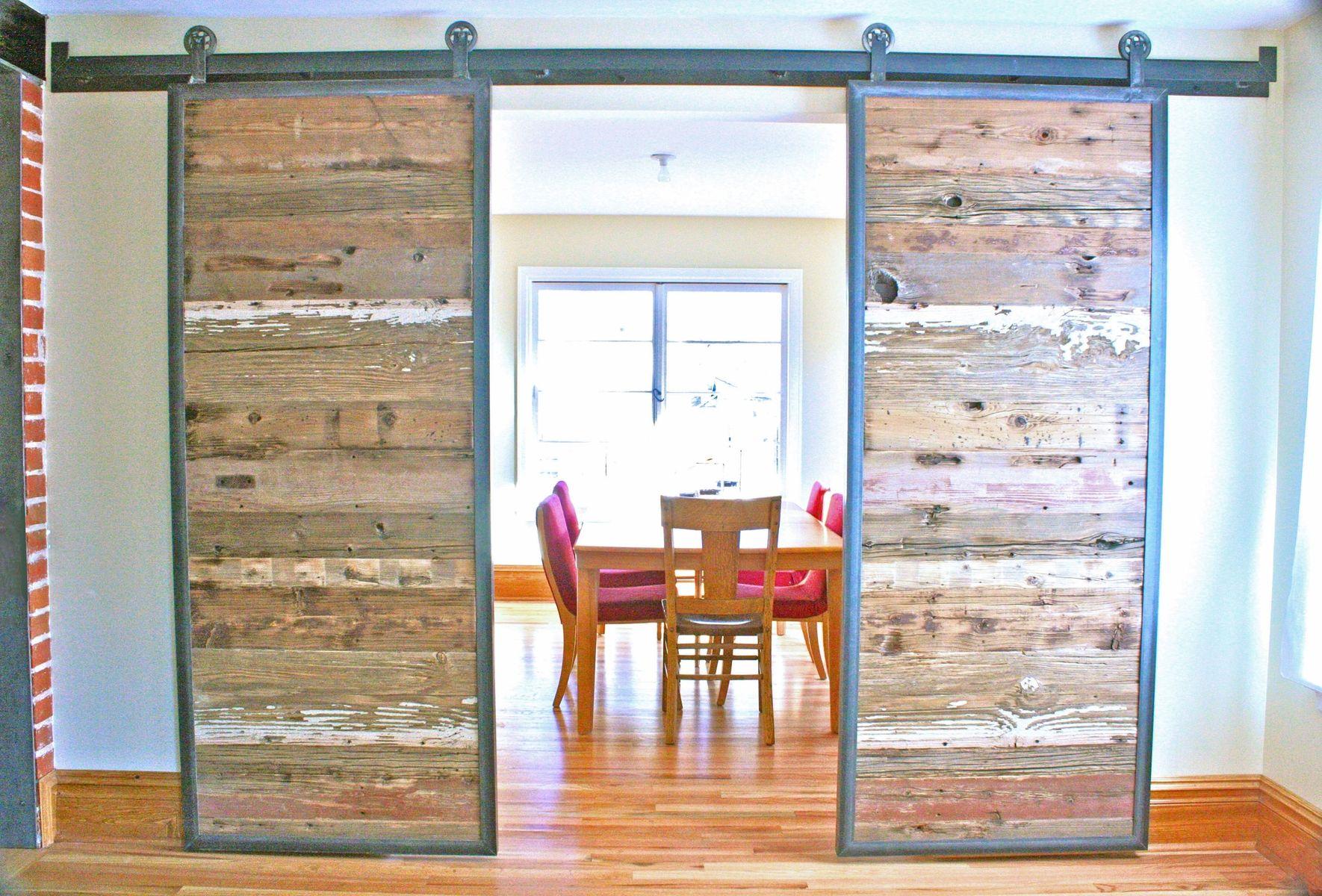 Lovely industrial reclaimed barn doors on a custom steel track