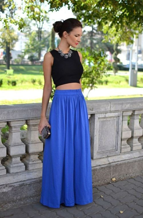 caa18baf62e56 Bright blue maxi skirt with a black crop top. Hair in bun with a short  necklace.