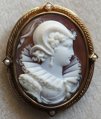 Elisabeth de Valois - Don Carlos Cameo    Material: Shell. 18 k gold and pearls.  Date: ca 1845  Origin: France  Size: 1 1/2 by s1 3/16 inch  Inclusive of the frame: 2 by 1 5/8  Condition: Mint         This cameo of surpassing beauty probably depicts Elisabeth de Valois (Fontainebleau, 1545 - Madrid, 1568) daughter of Henry II and Caterina de' Medici. Fiancée to Don Carlos, but bounded to marry his father, Philippe II.  The unlucky Elisabeth inspired many writers, at first Henry Shiller.