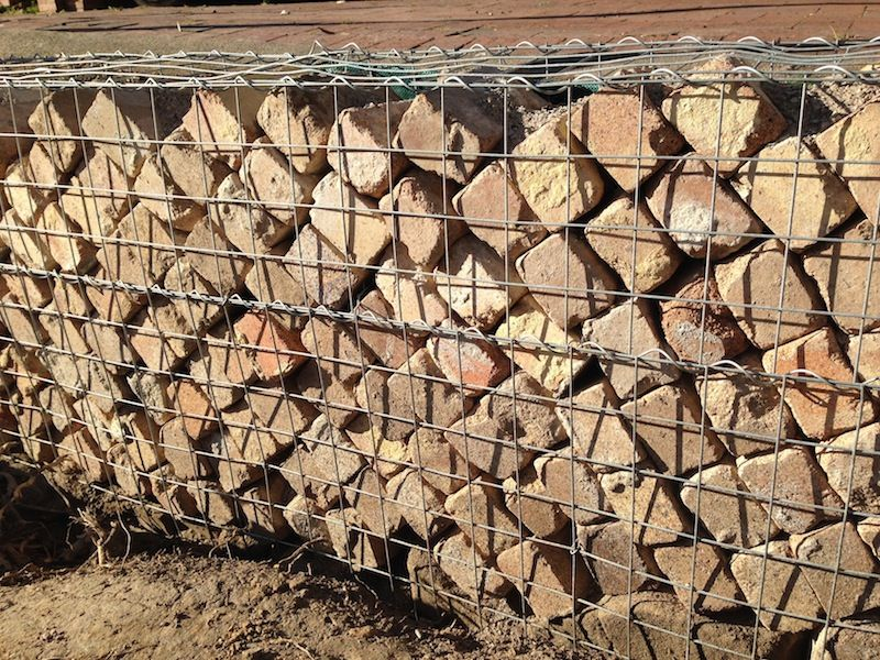 Old house bricks used as a gabion retaining wall filler for Uses for old bricks