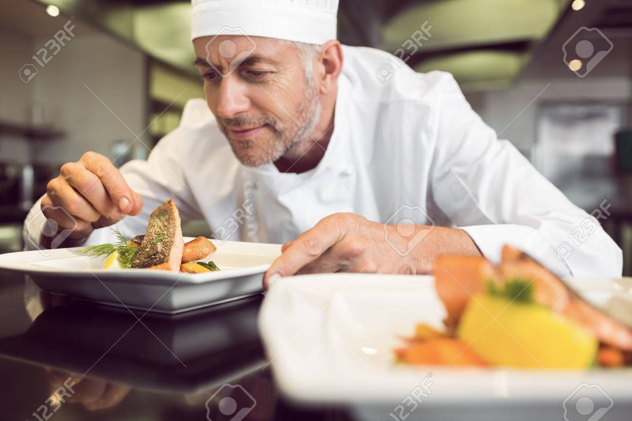 Closeup of a concentrated male chef garnishing food in the kitchen , #SPONSORED, #male, #concentrated, #Closeup, #chef, #kitchen