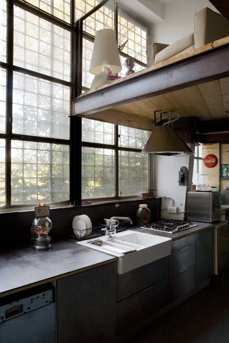 factory loft kitchen with gorgeous windows and a mezzanine over hanging the kitchen