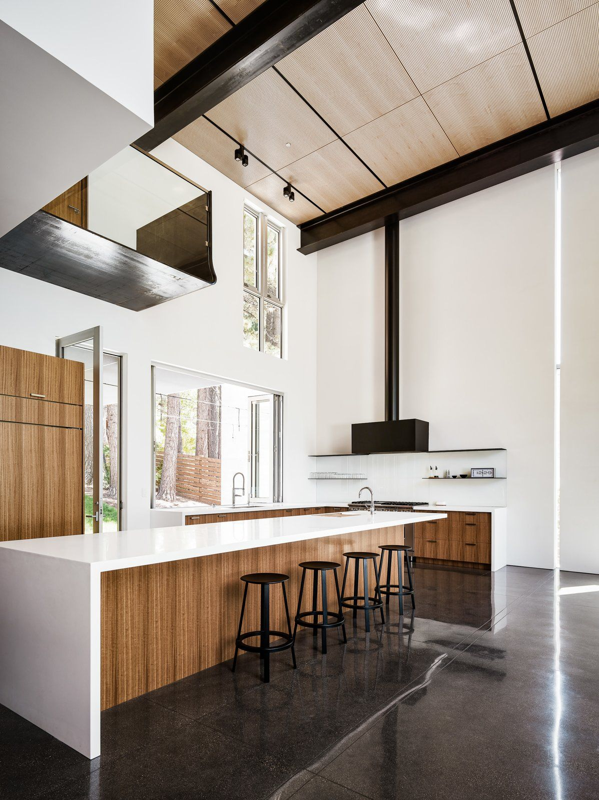 Kitchen concrete floor ceiling lighting wood cabinet and range hood operable doors and windows capture westerly breezes off the lake that flow through