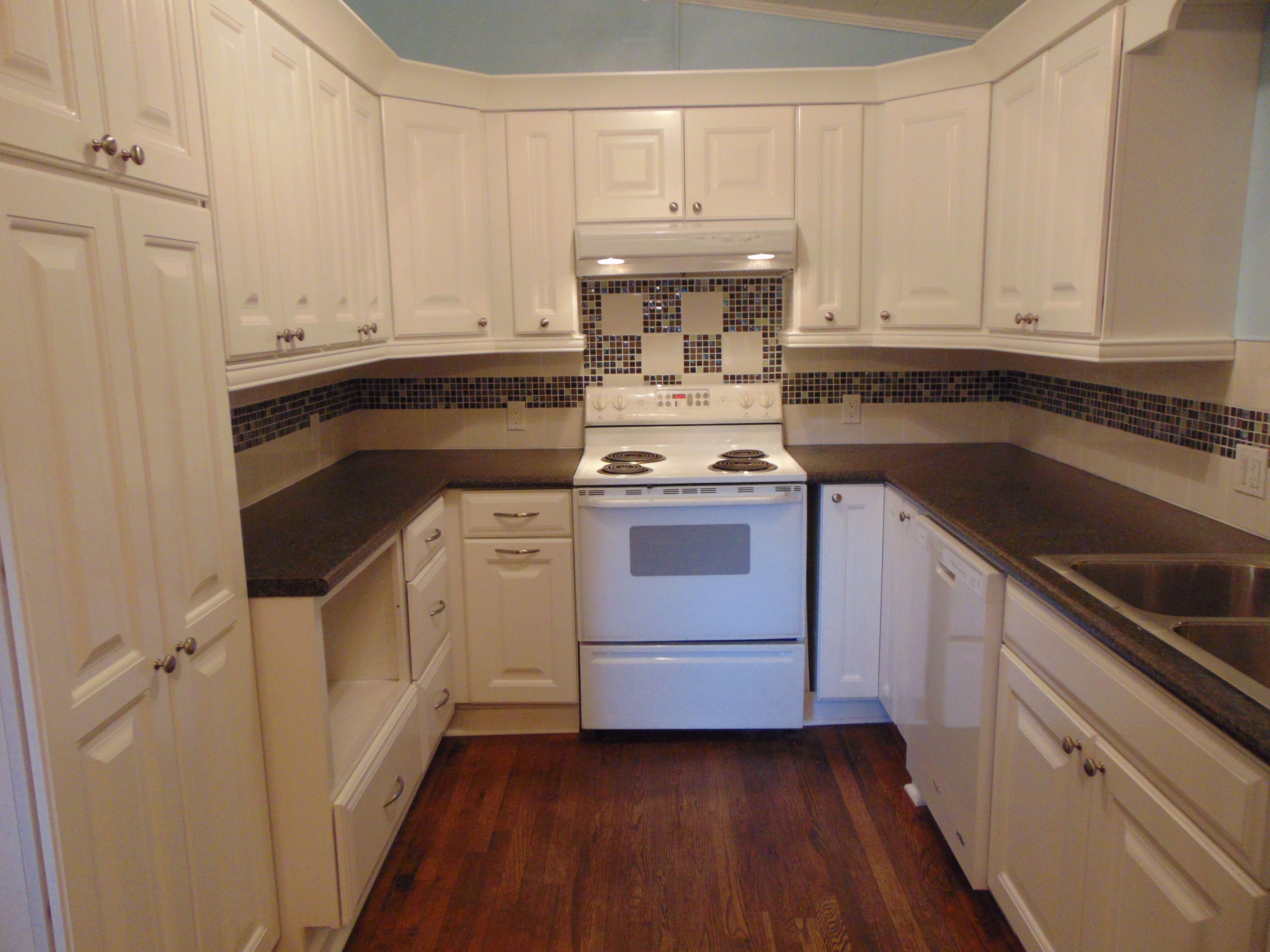 Remodeled kitchen is wheelchair accessible and features white