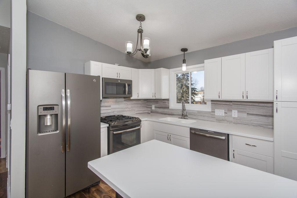 arctic white quartz. Contemporary Kitchen With Pendant Light, Flush, Arctic White Quartz, Shaker Recessed Panel Cabinets, Stone Tile, L-shaped Quartz E