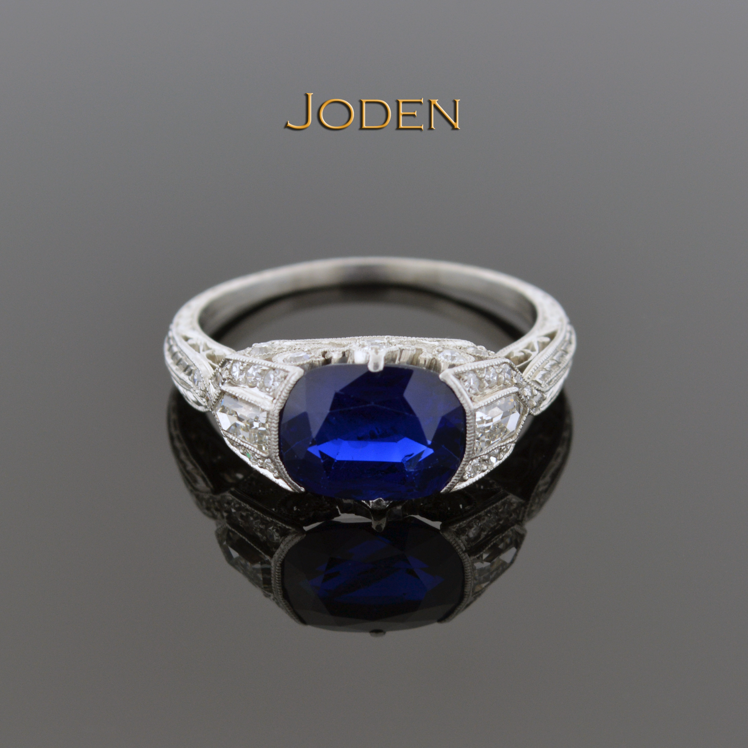 A beautifully cut oval sapphire sits east-west in this gorgeous Art Deco diamond…