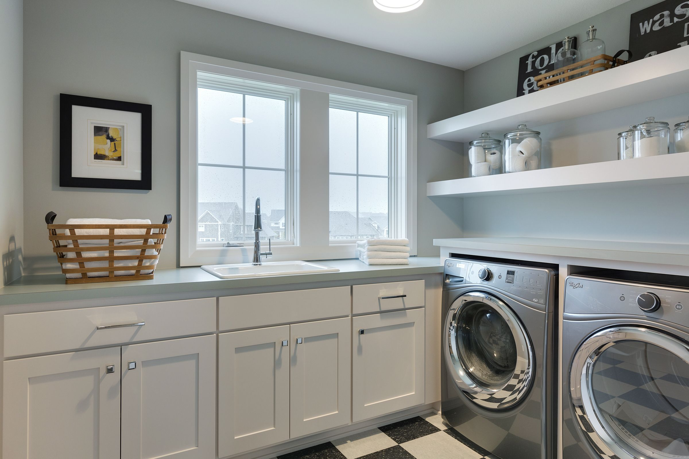 Upper level laundry with floating shelves and checkerboard tile