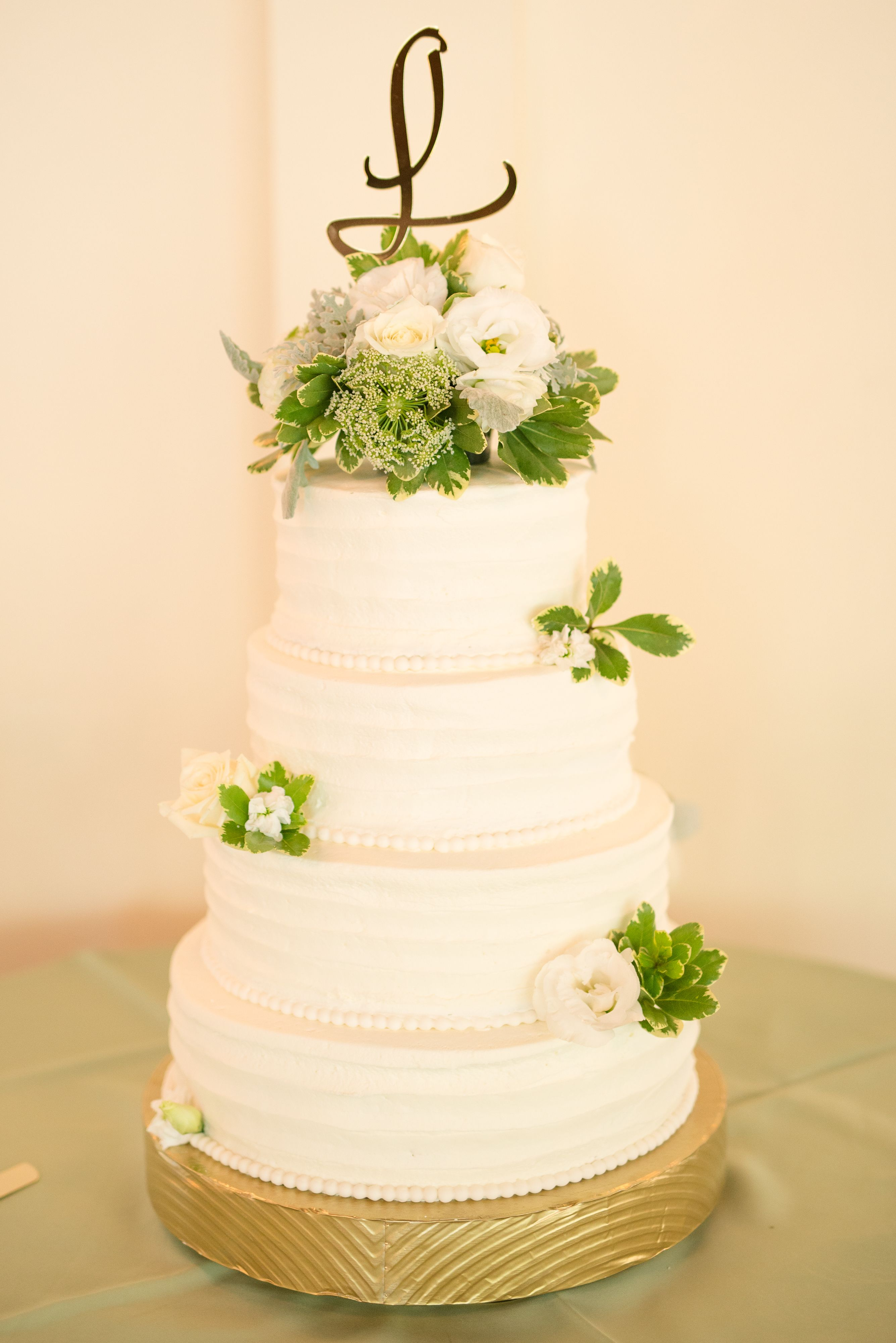 White Four Tiered Wedding Cake With Fresh Flowers And Greenery