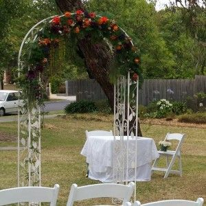 Metal wedding arch with orange and purple flowers. | The Wedding ...
