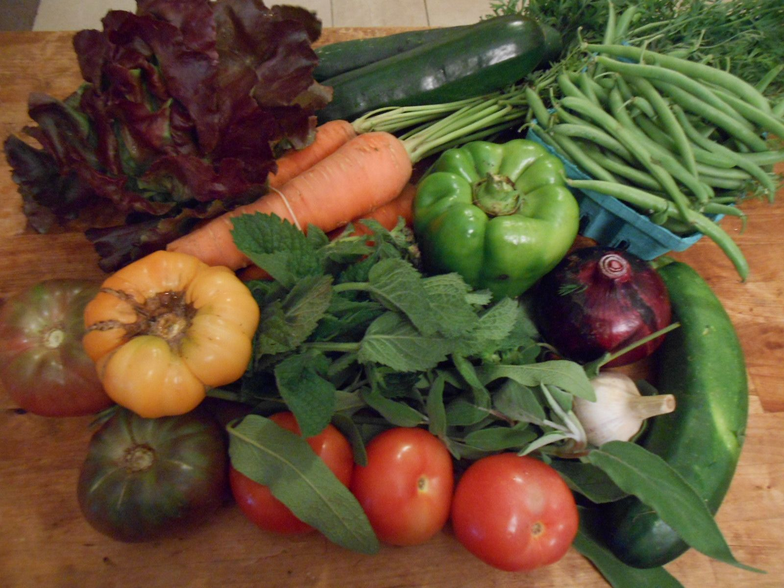 July 23, 2014: red butter lettuce, zucchinis, a cucumber, carrots with tops, green beans, a huge bell pepper, a red onion, a garlic, six gorgeous heirloom tomatoes, and big bunches of sage and mint. I'm full up on pesto, infused oil, and compound butter, so these herbs will become teas and syrups. The pepper will go to a work friend, since I'm allergic.
