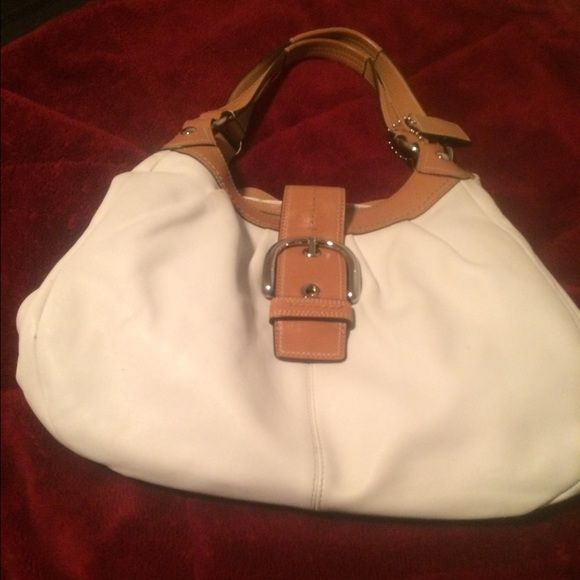 Authentic Coach handbag cream and tan  Authentic Coach handbag. The color is cream and tan with silver accents. This handbag is pre-loved and the condition is good. It has two closures one side zips the other snaps. The inside is spotless no stains or marks. The out side of the bag has one mark that is small . The bottom of the handbag has some superficial marks. These marks does not affect the beauty of the bag. The iD #D1069-F15075 the handbag is 15W top to bottom 11' strap 15'✅Please see…