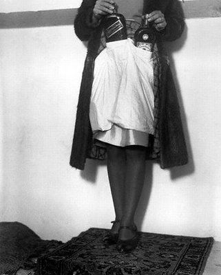 Bermuda -- A woman demonstrates how American tourists hide and smuggle liquor from non-Prohibition lands into the United States past customs. Under her skirt the woman wears a secondary skirt, with pockets for the alcohol. (1930)