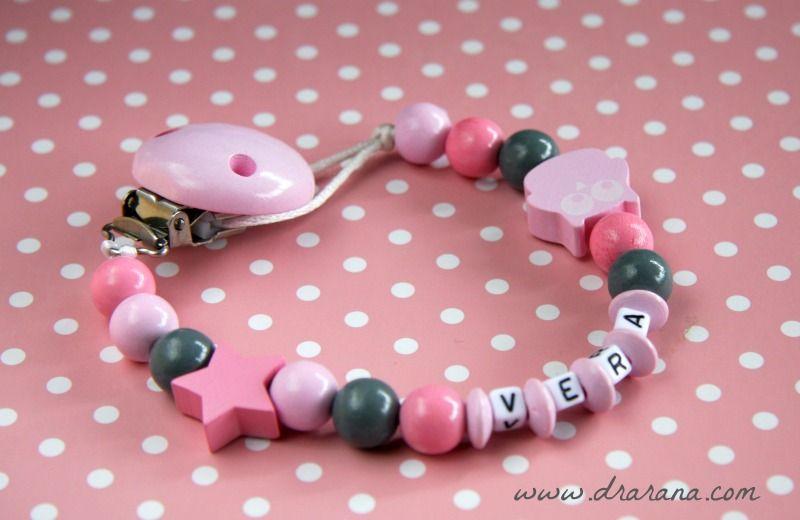 Chupetero de madera en dos tonos de rosa y gris. Personalizado con el nombre del bebé y cuentas en forma de estrella y buho.