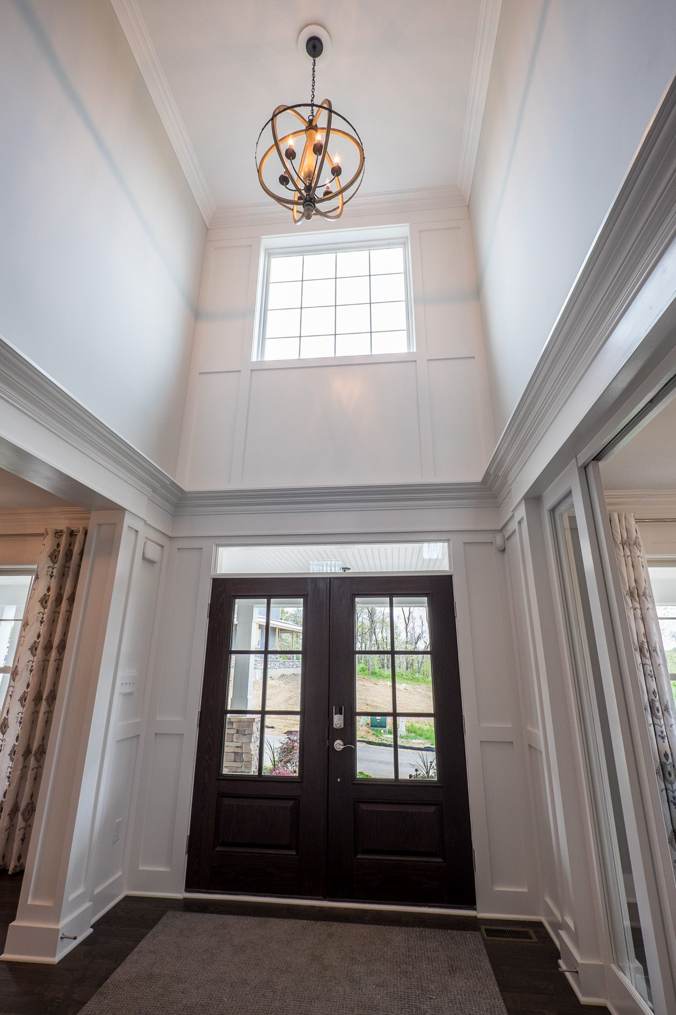 Window and a orbital light fixture brighten the 2 story for House plans with foyer entrance