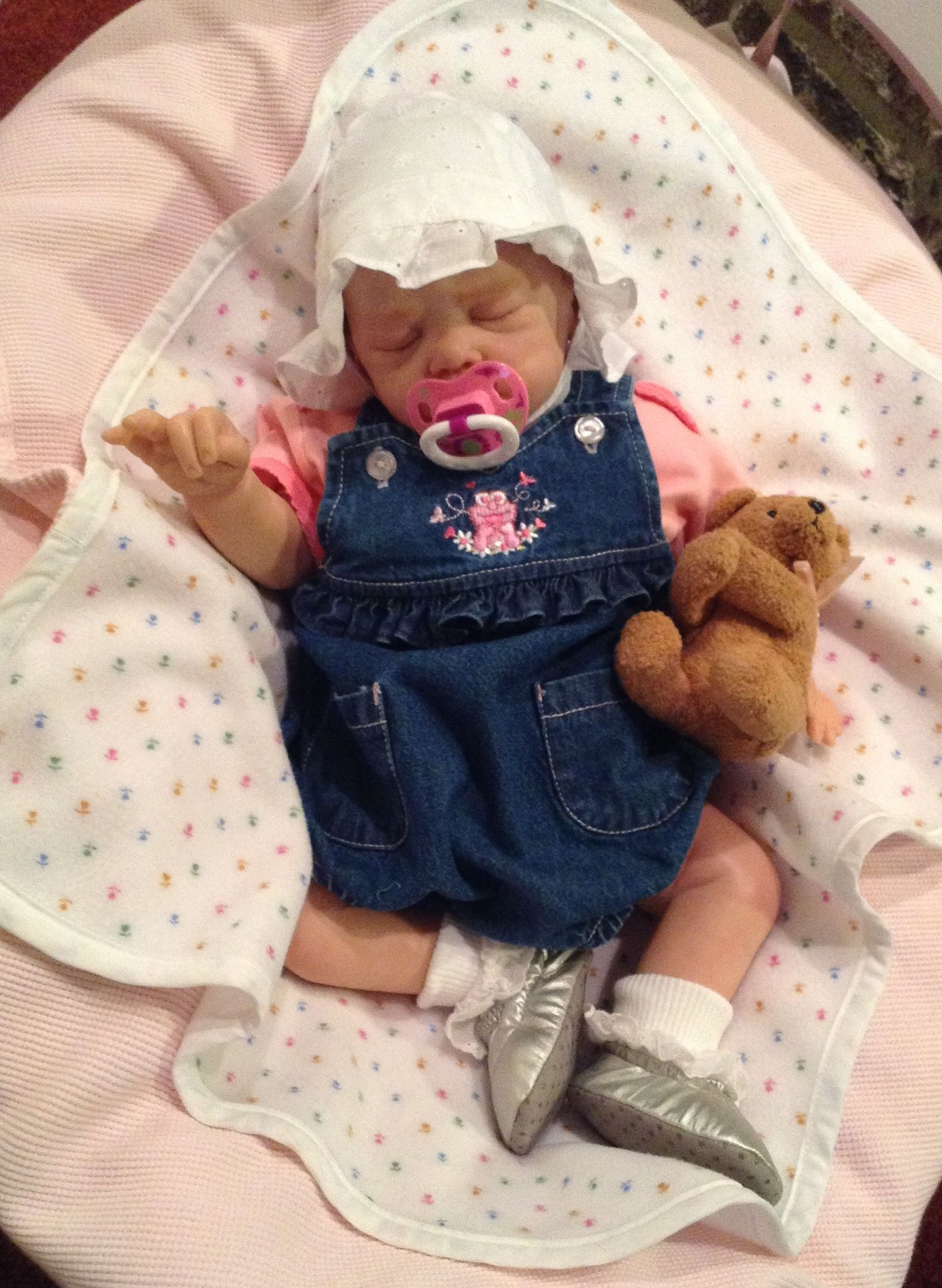Lillie Beth, reborn baby doll,  dressed for day camp with Mommy and Daddy. In denim overall romper and eyelet bonnet, matched with eyelet trimmed socks, she will be cool and comfy in the out of doors