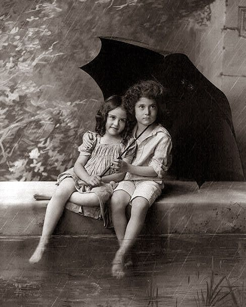 a sweet picture from 1902 showing two children with an umbrella