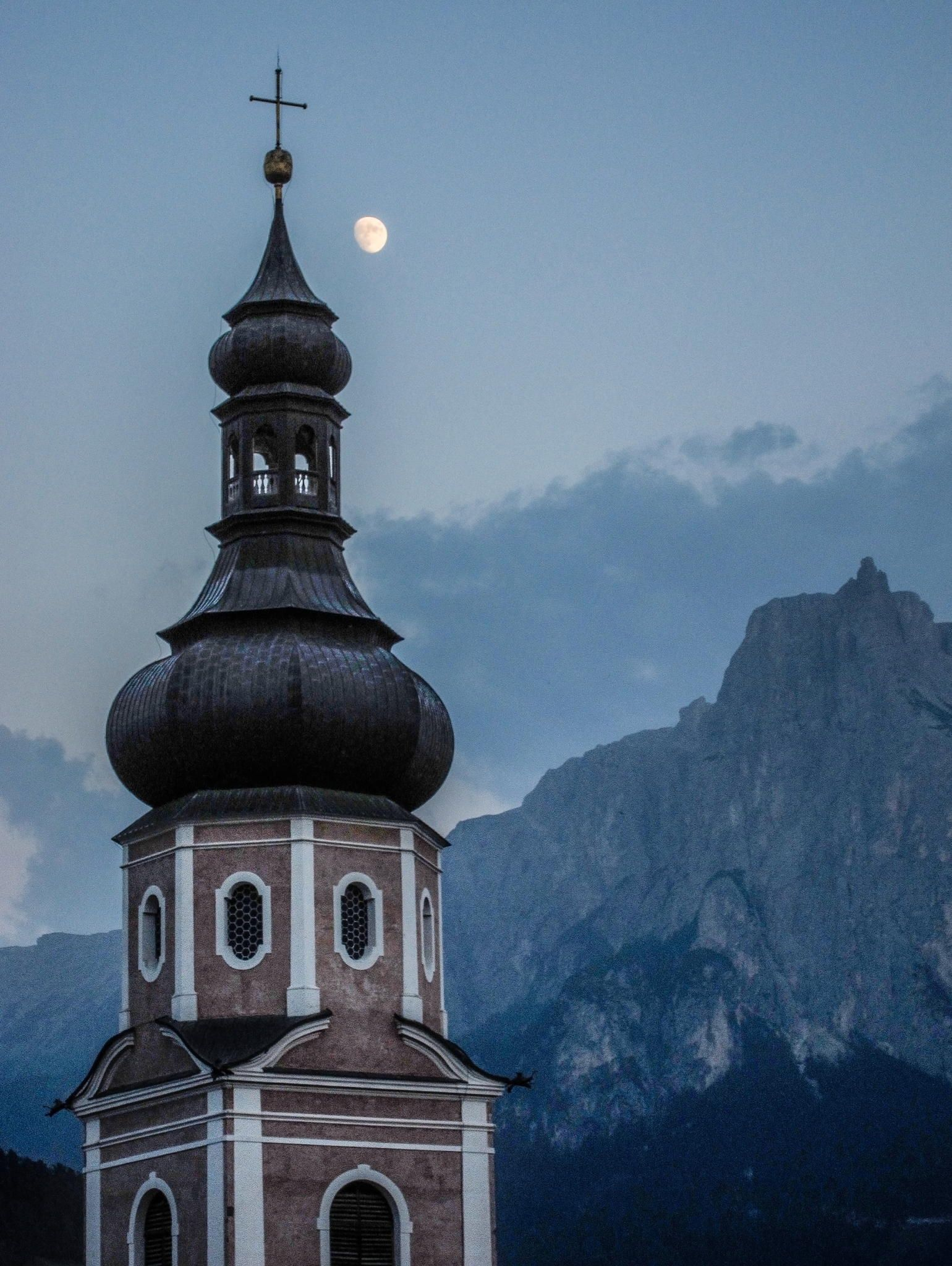 moon + steeple of the parish church of st. peter and paul, castelrotto (kastelruth), south tyrol, italy