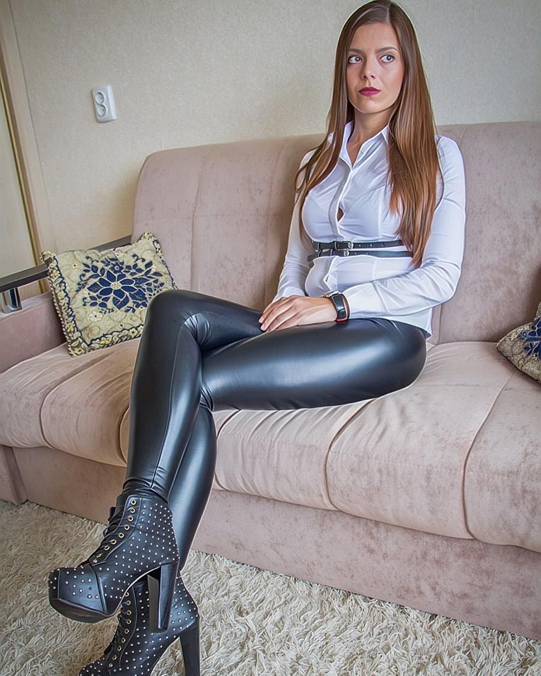amateur model in leather strap harness corset leather leggings and ankle boots sitting on couch. Black Bedroom Furniture Sets. Home Design Ideas