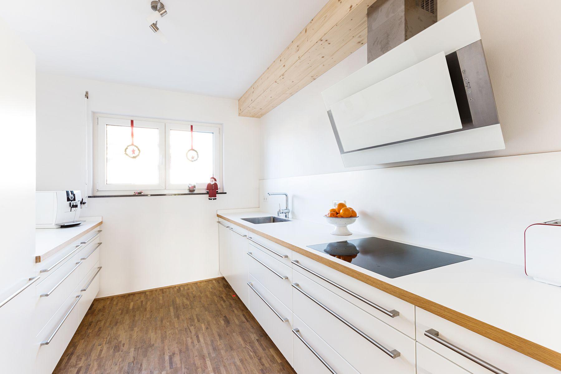 Elegante weiße Küche mit heller Arbeitsplatte und Kanten
