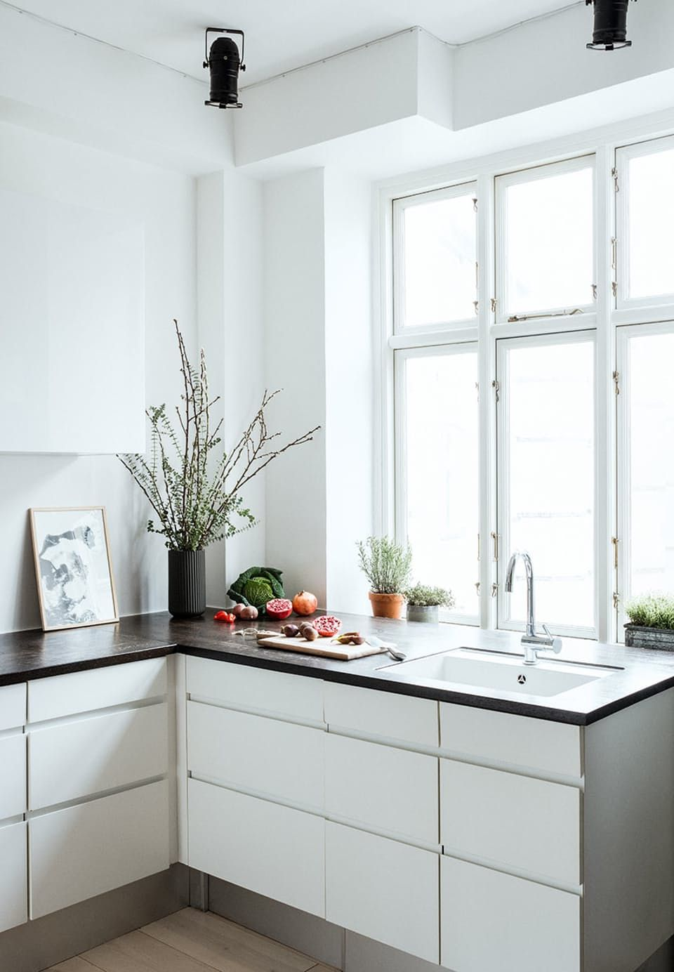 White kitchen with black stained tabletop - minimalistic with space to decorate as one like.