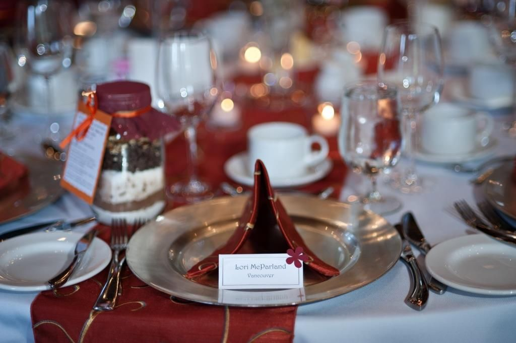 Table Settings With Burnt Orange Napkins, Silver Chargers, Cookie Dough  Wedding Favors In Mason