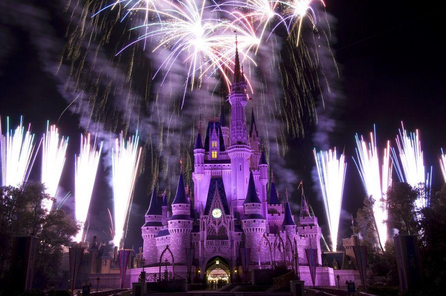 Purple & Blue castle with surrounding fireworks Disney