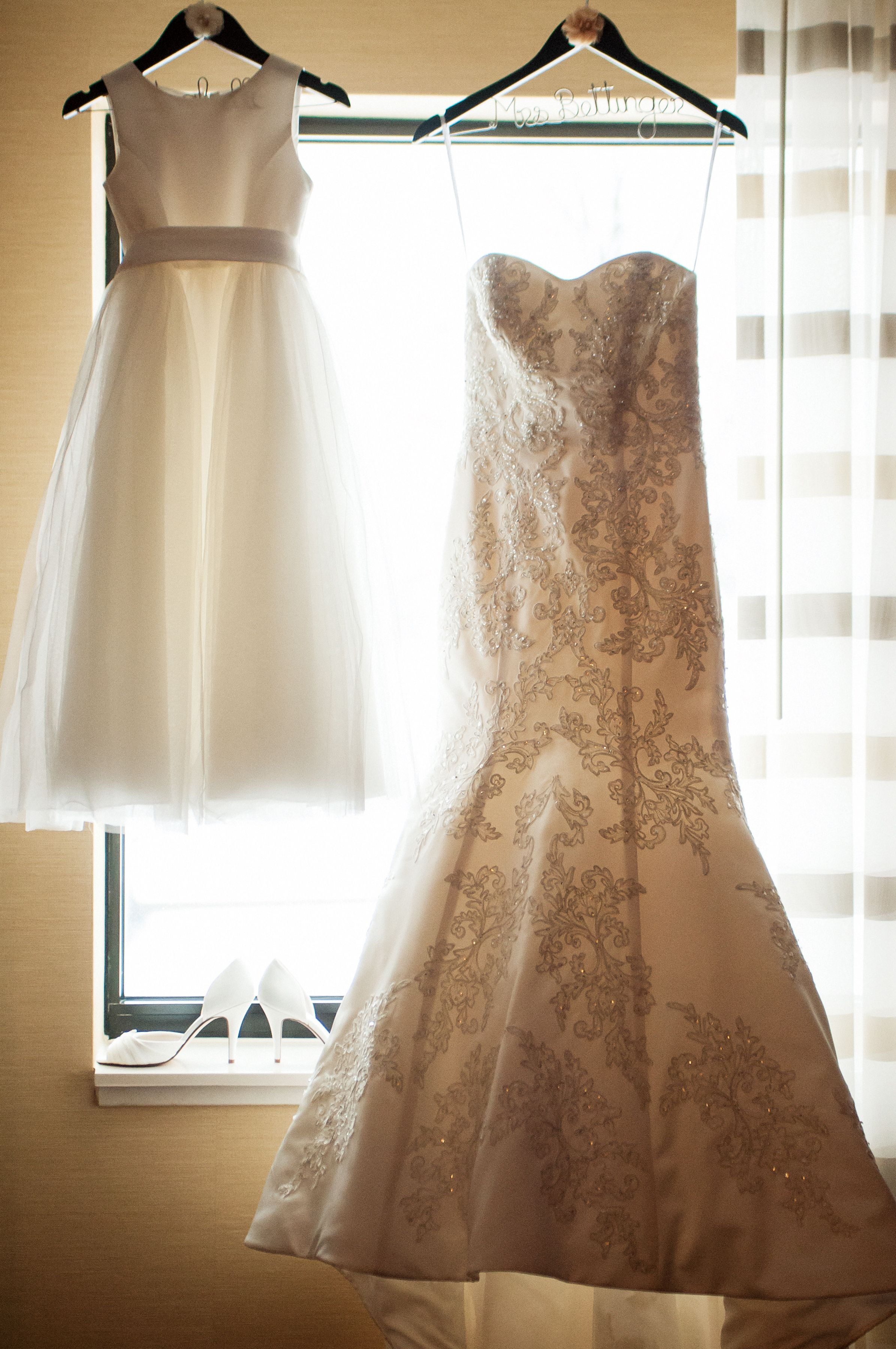 A wedding gown and flower girl dress hang beside each other in a ...