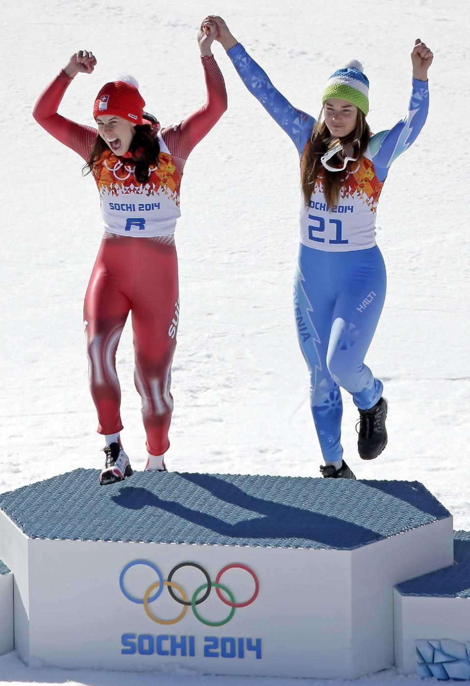 Women's downhill gold medal winners Switzerland's Dominique Gisin, left, and Slovenia's Tina Maze step onto the podium together during a flower ceremony at the Sochi 2014 Winter Olympics, Wednesday, Feb. 12, 2014, in Krasnaya Polyana, Russia. (AP Photo/Charlie Riedel)