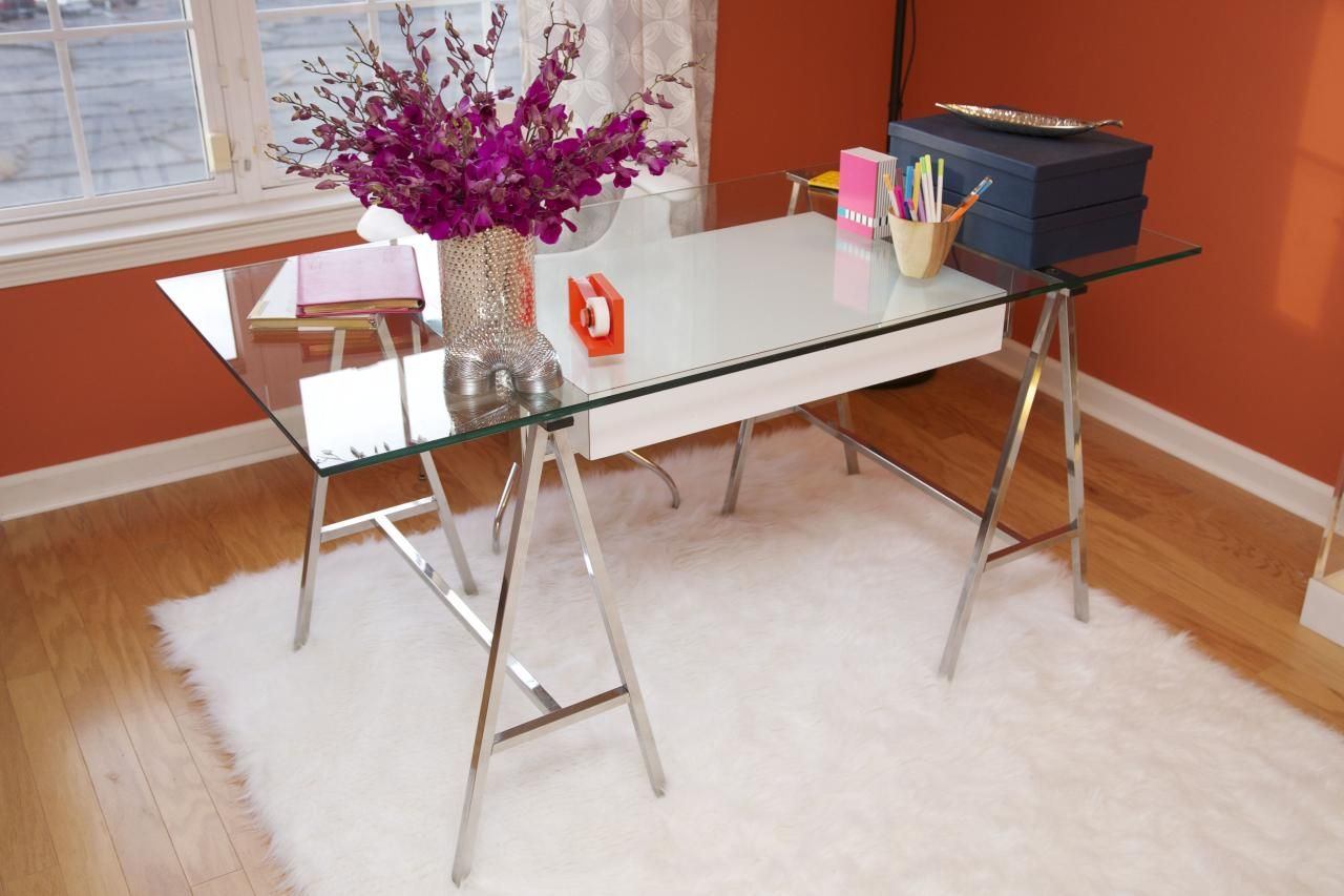 glass desks for home office chrome this modern home office features vibrant orange walls and glass desk accented by white faux fur area rug purple flowers gray organizational boxes