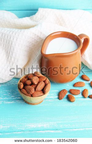 Almond milk in jug with almonds in bowl, on color wooden background by Africa Studio, via Shutterstock