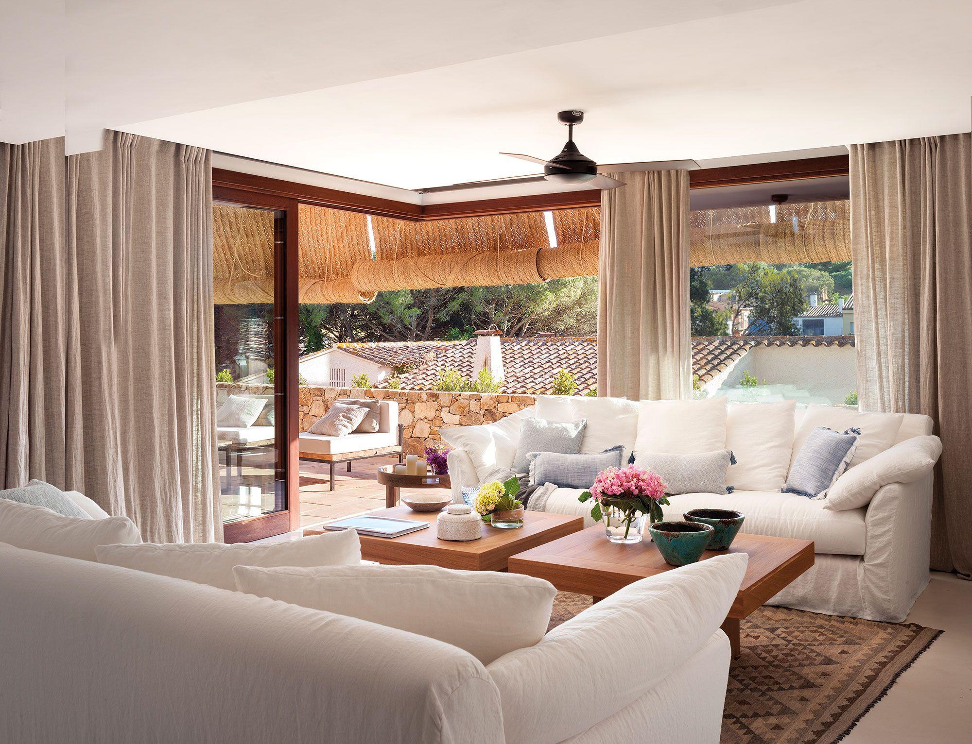 Salón con sofás en blanco y gran ventanal con vistas a la terraza