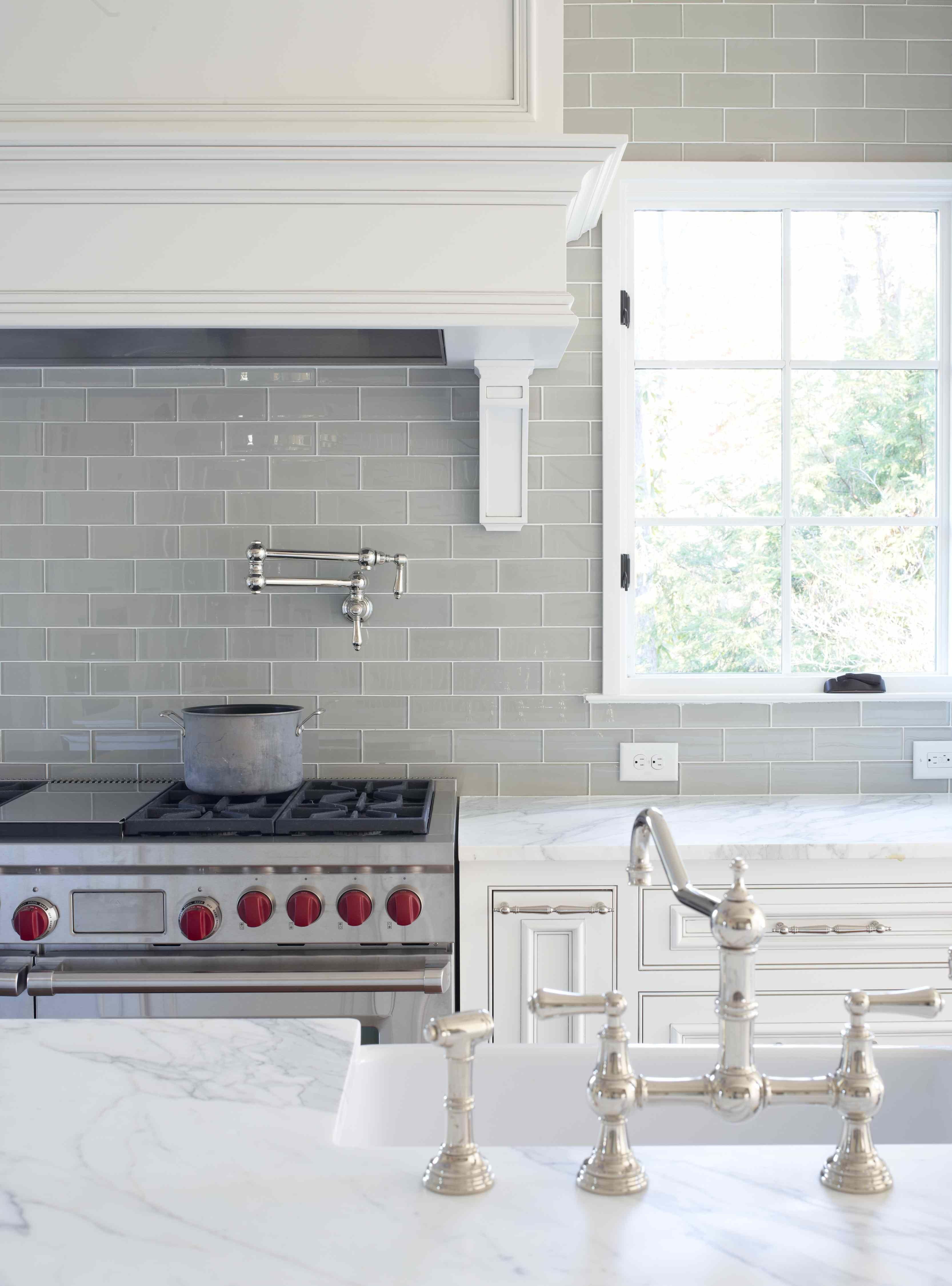 Smoke gray backsplash white cabinets and carrera marble countertops also glass subway tile grey