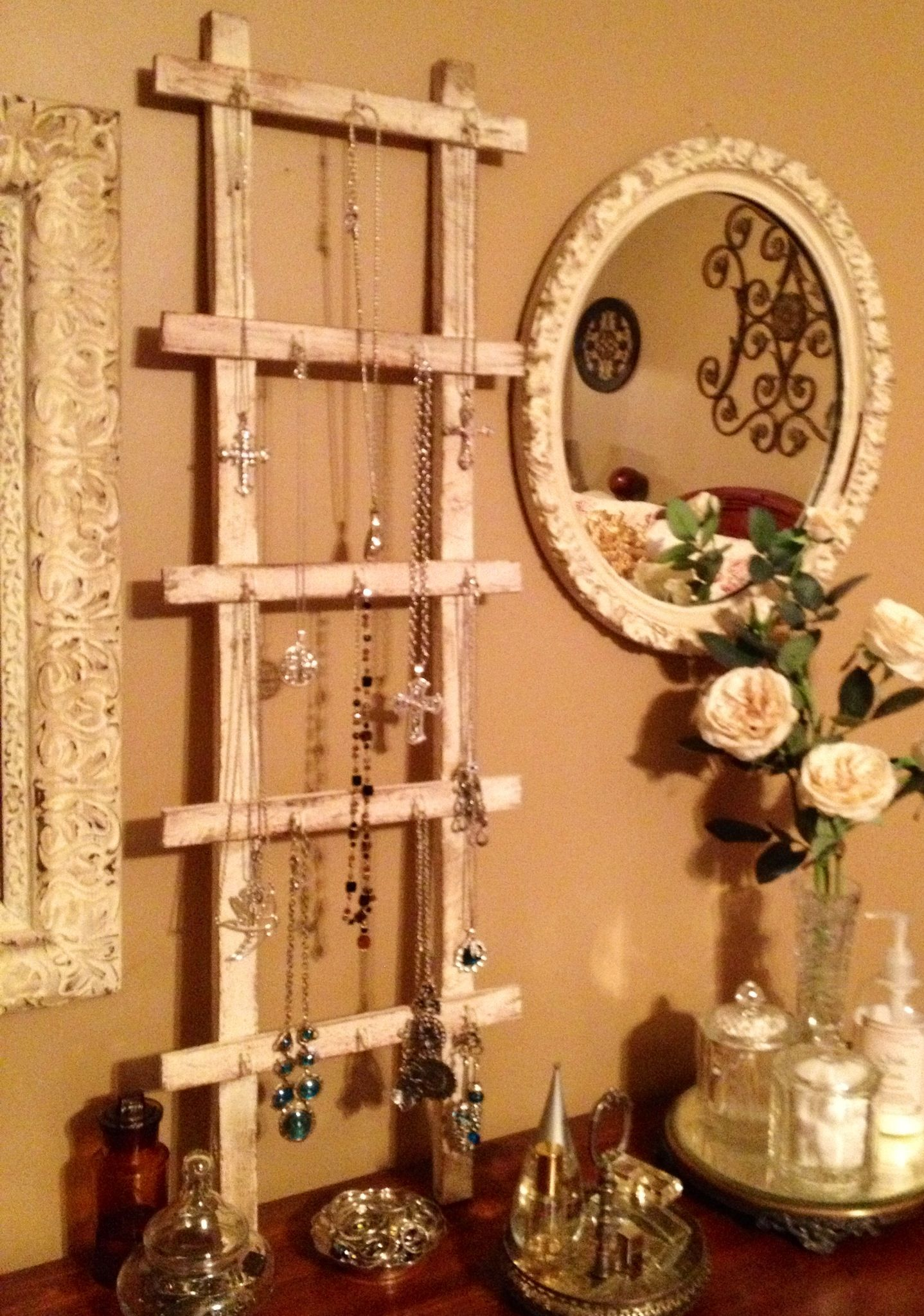 I painted this small trellis, rubbed it rustic and added a few hooks to make a $2 Jewelry holder. #DIY