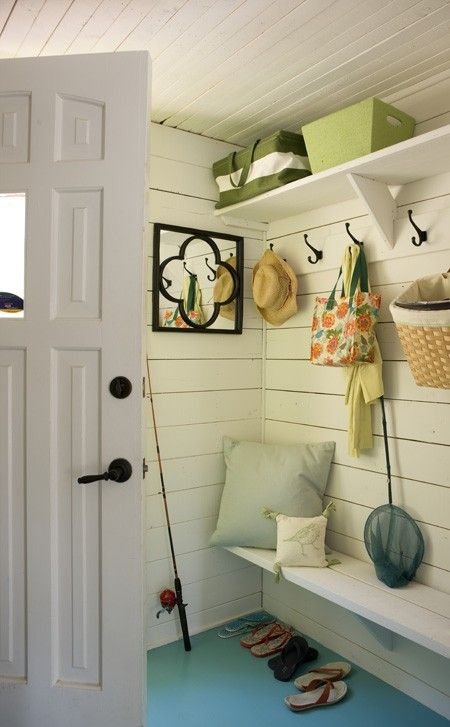 Casual Cottage Entryway  In this Laurentians, Que. cottage, a cramped mudroom feels larger thanks to white paint and a teal painted floor. Homeowner Heidi Smith installed the hooks and shelving herself for convenient storage.