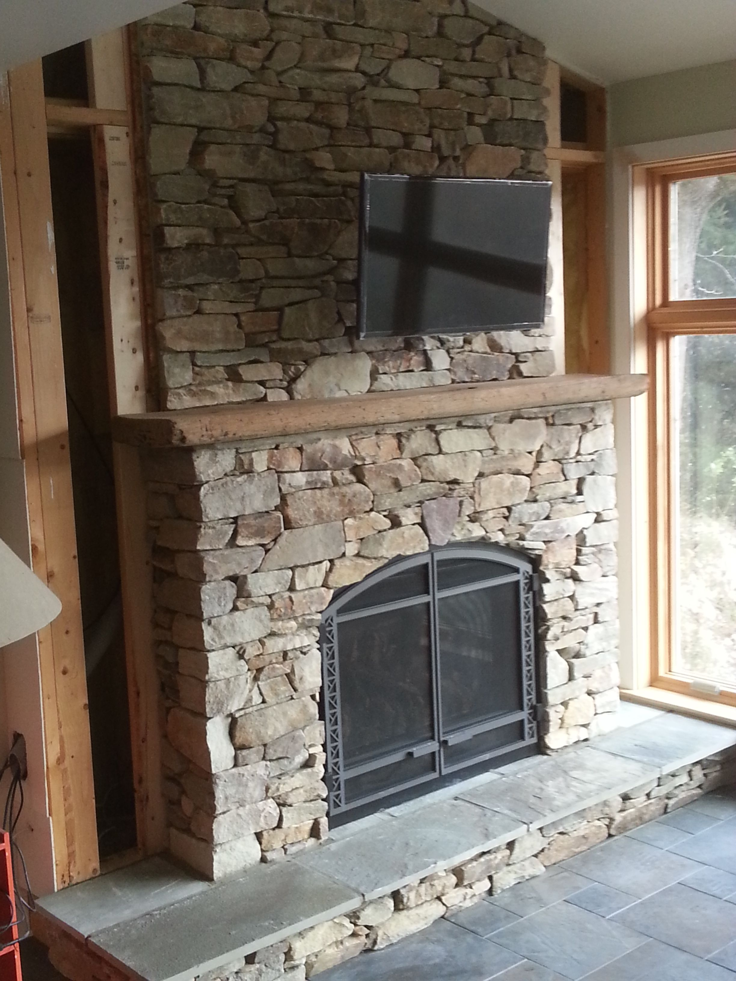 Fireplace Surround Using Natural Veneer Stone With A Cut Bluestone Hearth And Chestnut Barn Beam