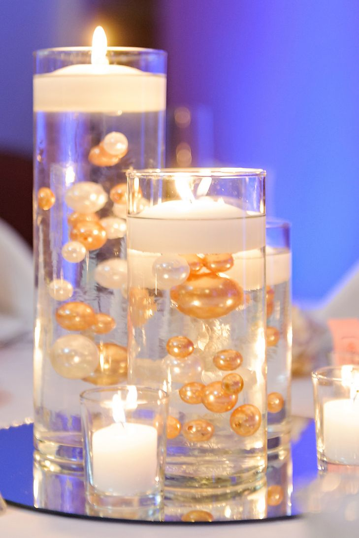 Floating candle centerpieces with gold and white pearls wedding the centerpieces included vases of varying heights filled with gold and white pearls and topped with floating candles reviewsmspy
