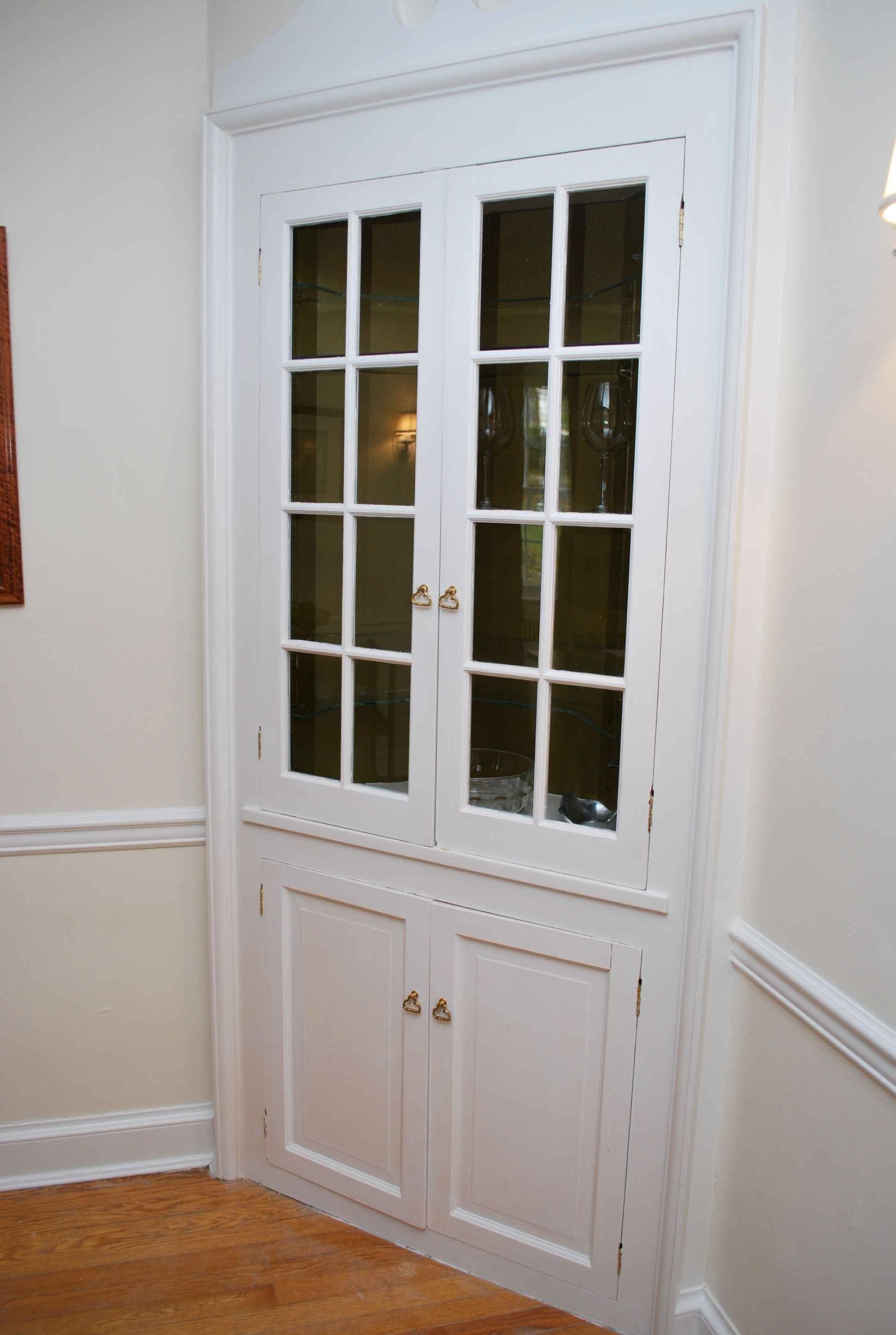 another built in corner cabinet with an arched window and more