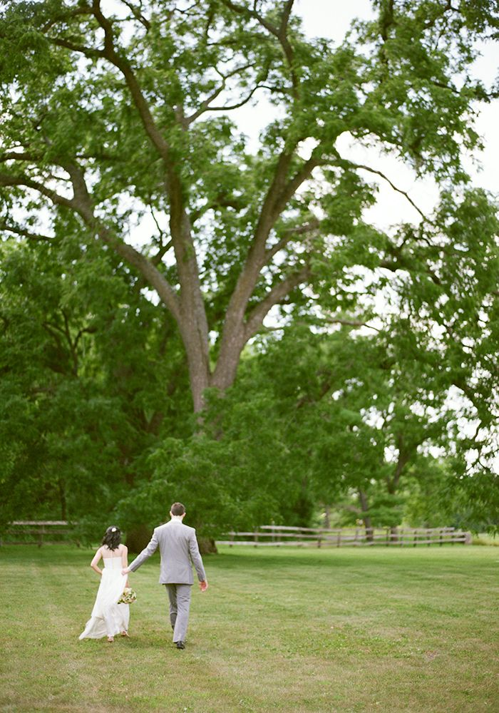 bride and groom walking together in the country | trees and wood fence | Mayowood Stone Barn wedding | Photo: Laura Ivanova Photography