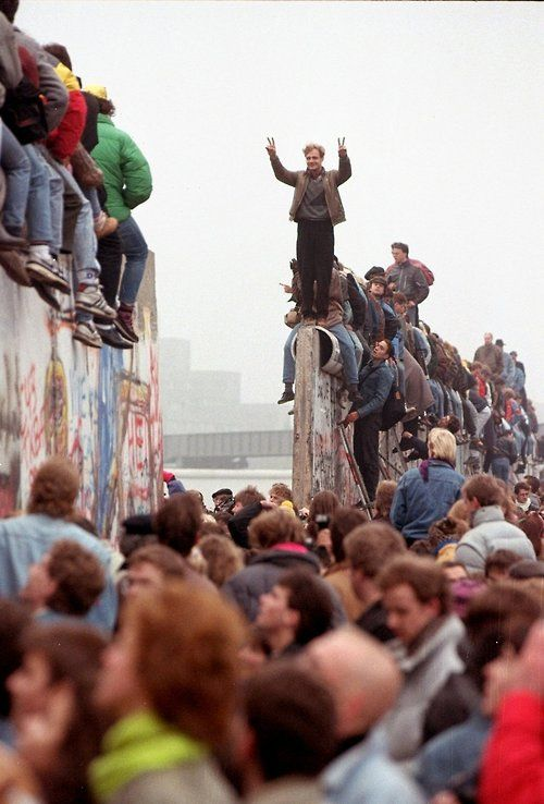 Image result for germans on top of berlin wall as communism crumbles in eastern europe
