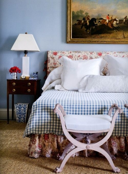 Sky blue walls are the perfect backdrop for red floral, country gingham, sisal, and a hunt scene above the headboard in this bedroom in Gil Schafer's own home.