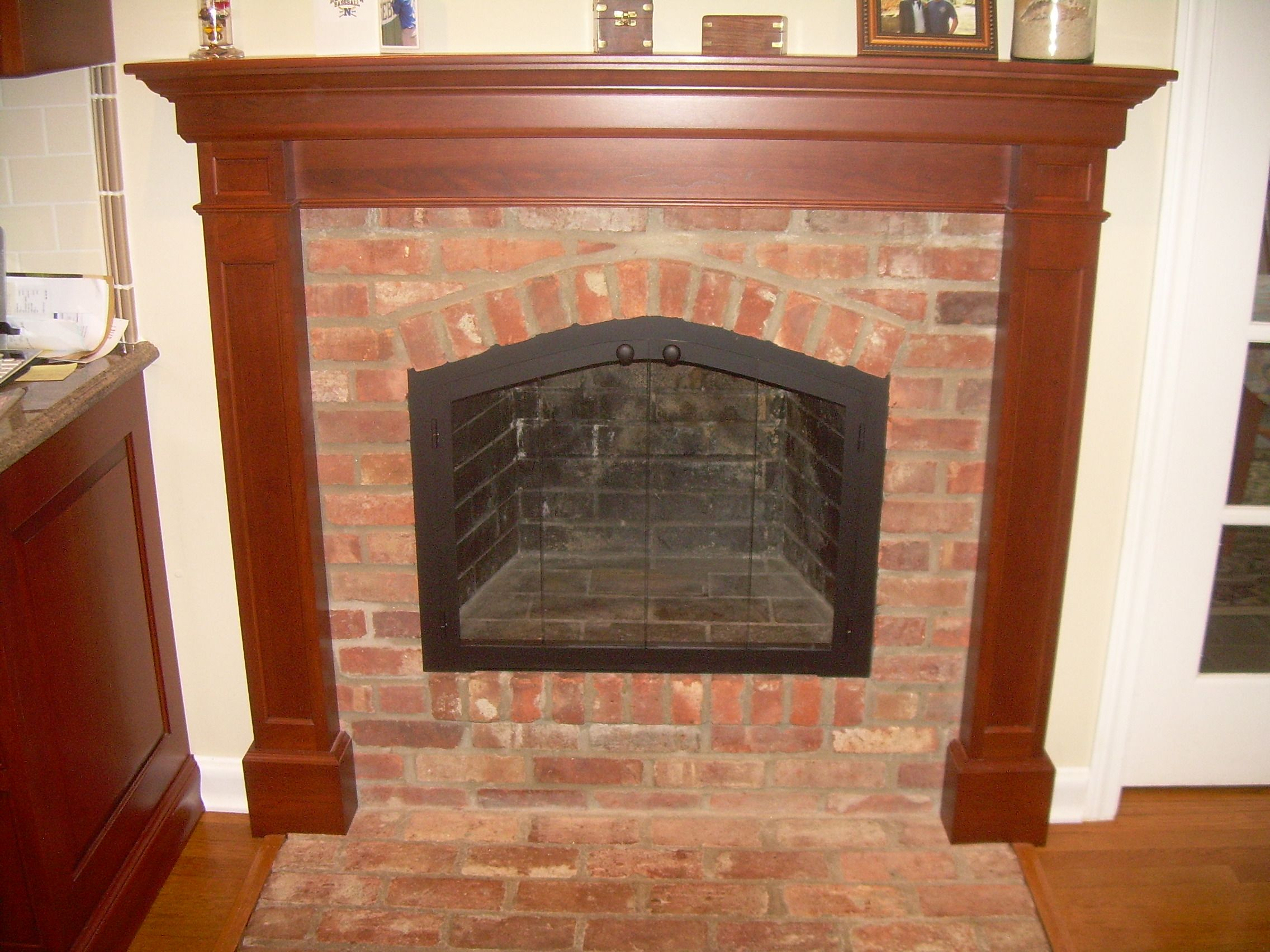 A brick arched fireplace with custom glass doors fireplaces
