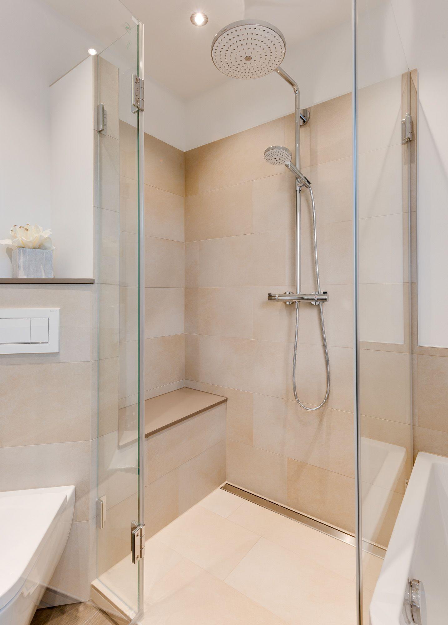 Geräumige Dusche mit integriertem Duschsitz und einer