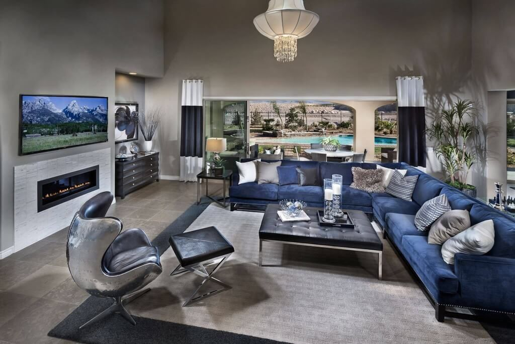 Expansive Open Living Room On Grey Tile Flooring Features Lengthy Blue Fabric Sectional Sofa And Chrome B Silver Living Room Living Room Grey Blue Living Room #royal #blue #sectional #living #room