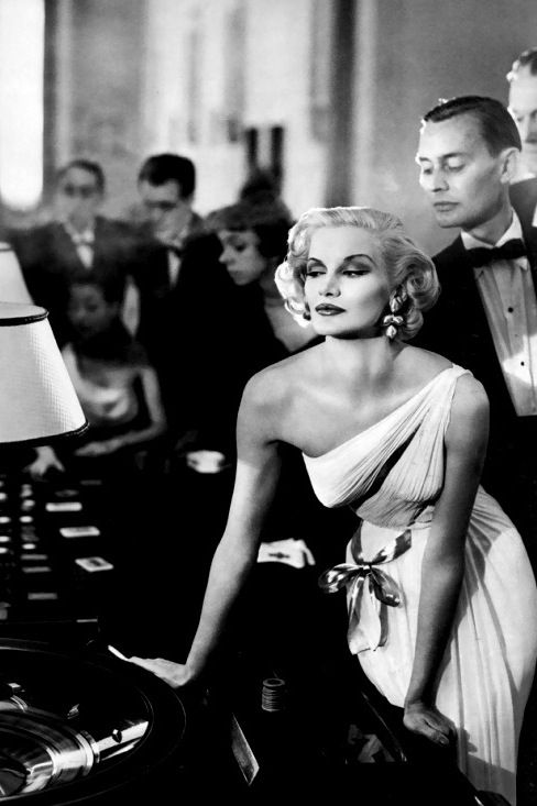 Sunny Harnett in evening gown by Grès at the gaming tables in the Casino at Le Touquet photo by Richard Avedon August 1954