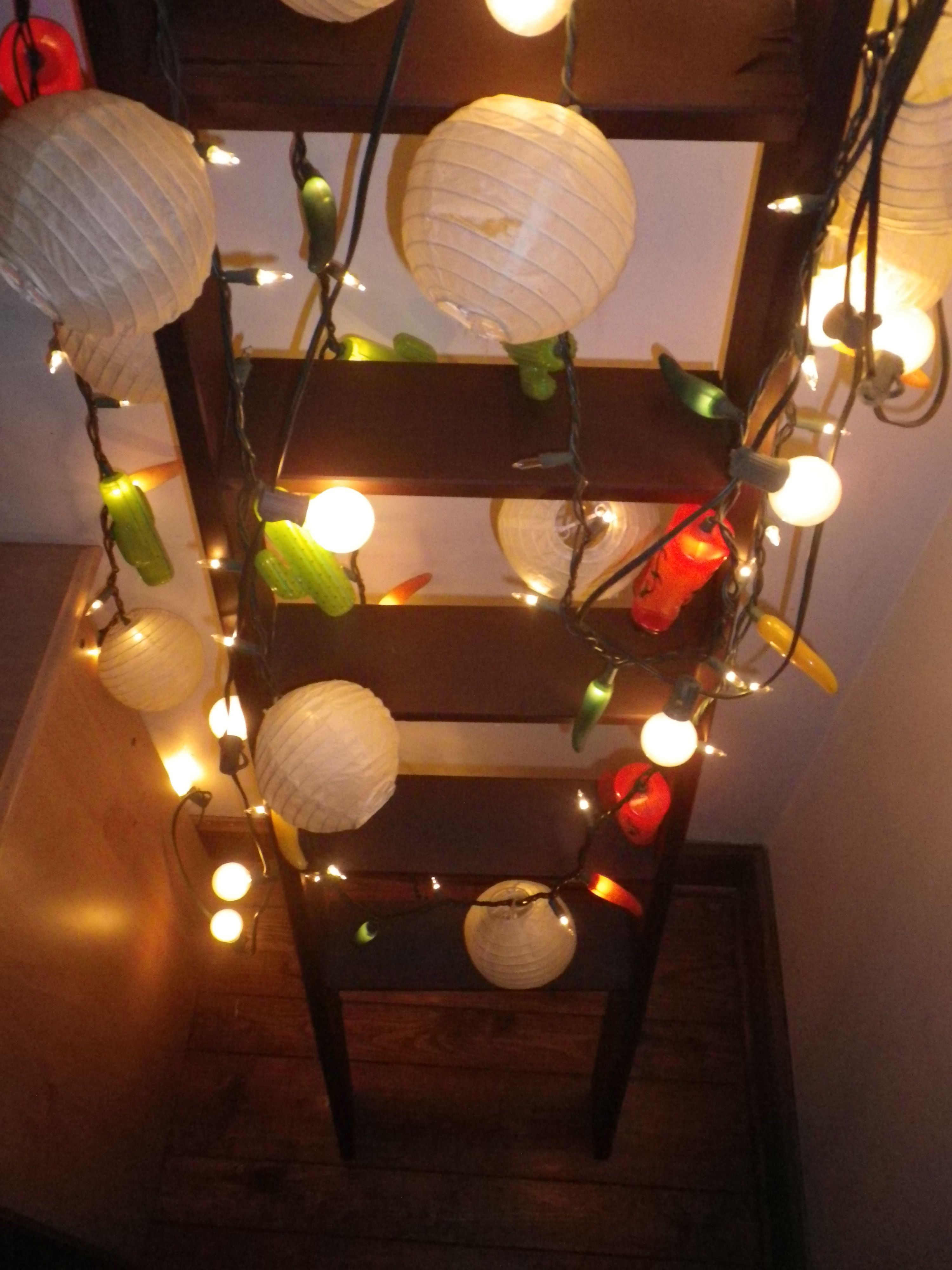 creative lighting display lighting lanterns display home decor assorted cacti cowboy boots and chili peppers on ladder