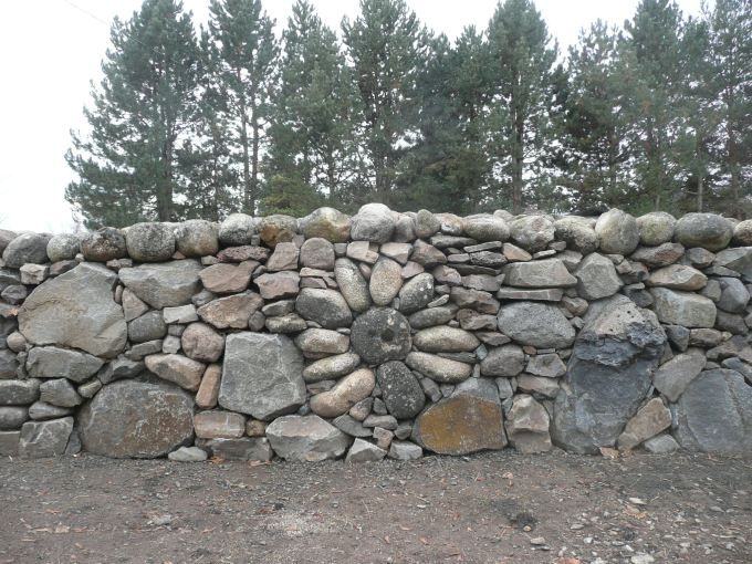 Rock Walls Landscaping | Stone flower design built into drystacked basalt  retaining wall