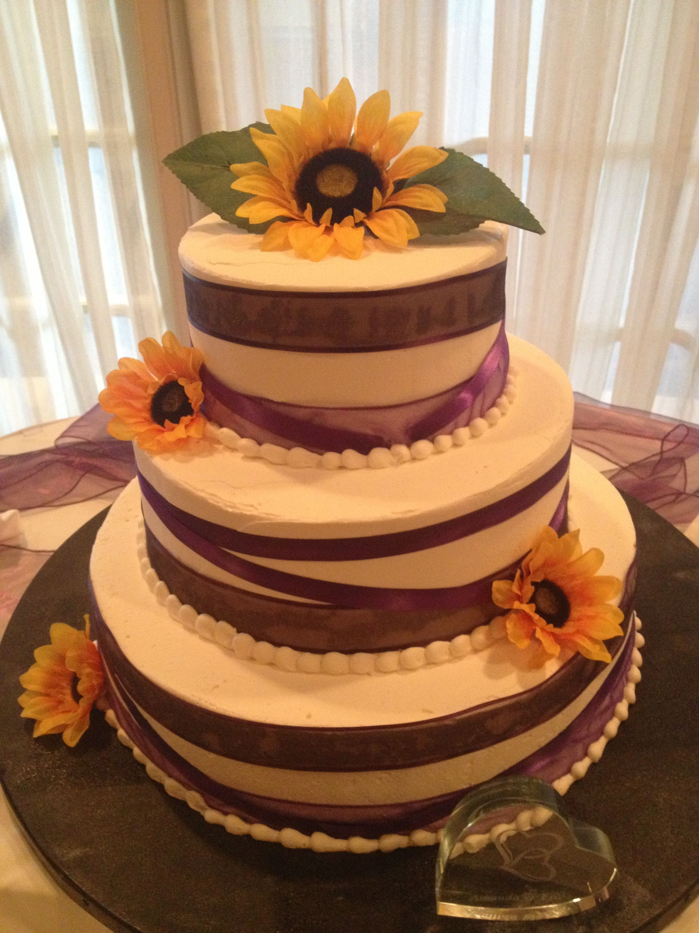 White wedding cake with purple ribbon and yellow
