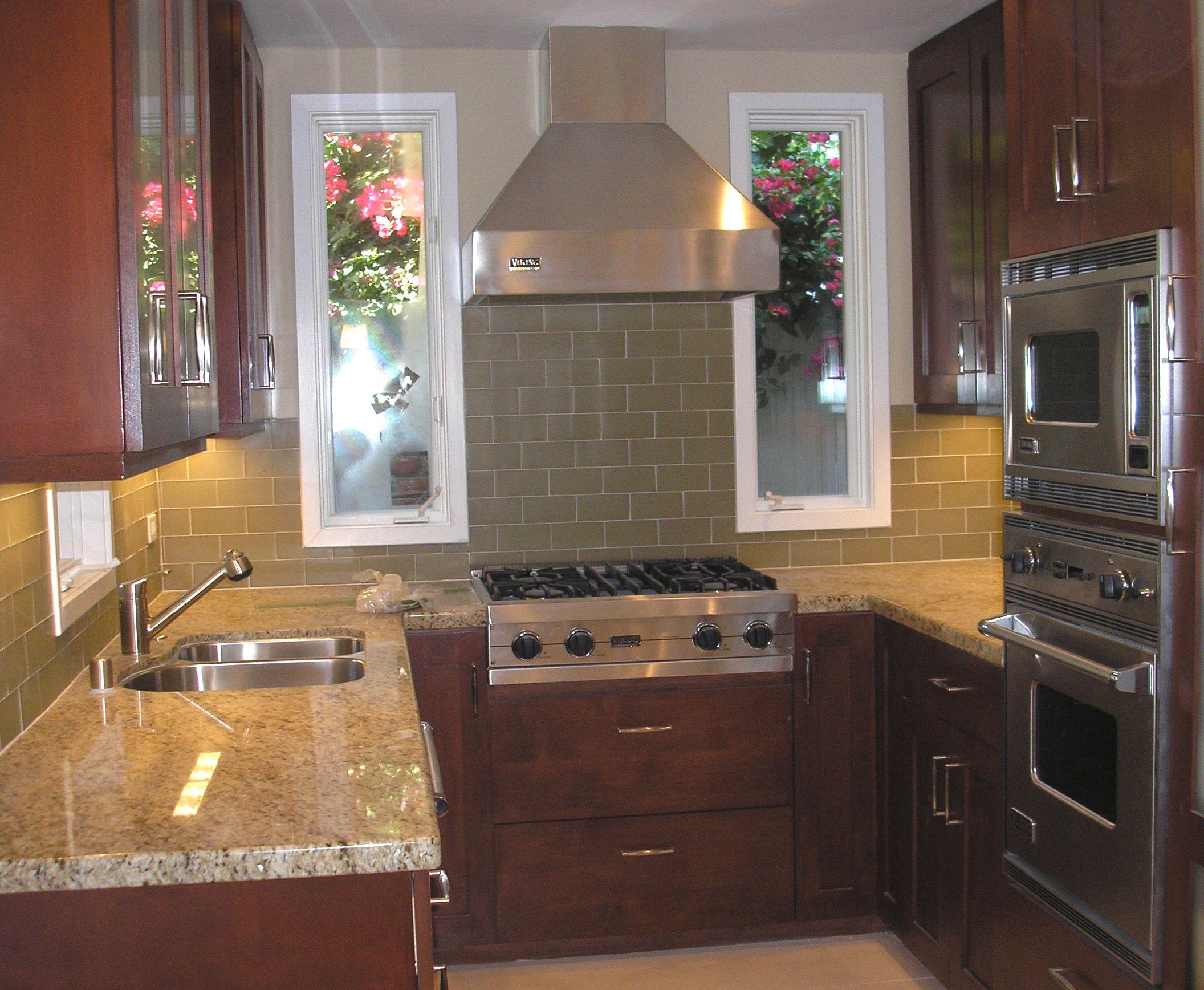 Small Custom Kitchen With Sage Green Glass Subway Backsplash Stainless Steel Appliances Chocolate Bro Interior Design Kitchen Kitchen Design U Shaped Kitchen