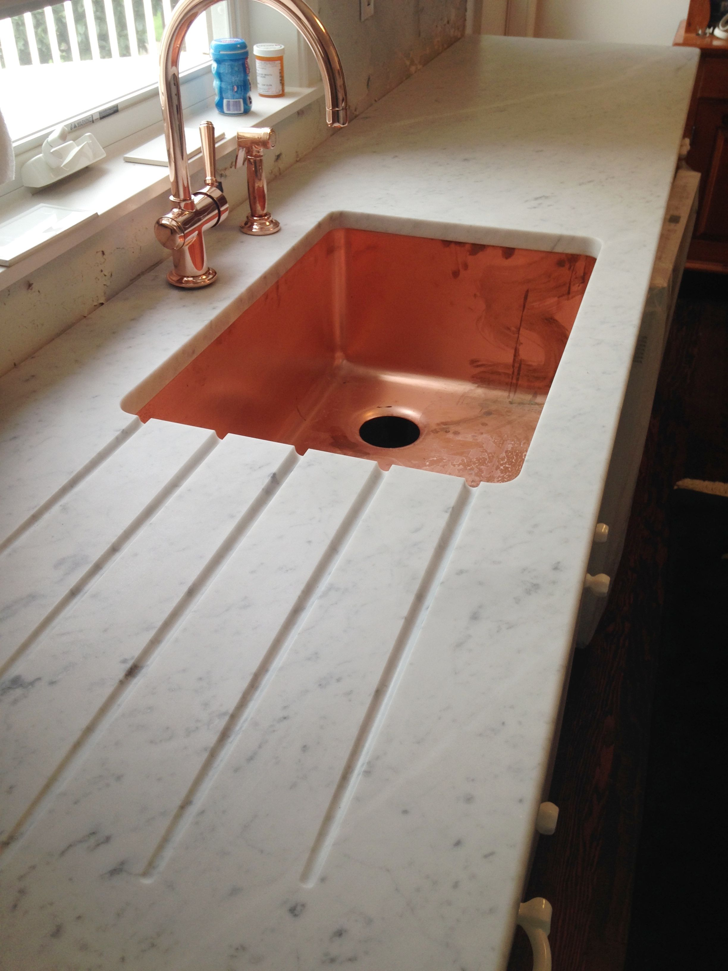White Carrara Marble Kitchen Countertops With A Grooved Drainboard And Copper Sink Faucet